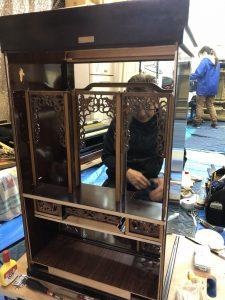 唐木仏壇 洗浄  唐木仏壇  お仏壇洗濯はやすらぎ工房にお任せ下。唐木仏壇も伝統技術でお仏壇の洗浄・洗濯致します。唐木仏壇 使用する材木が紫檀・黒檀等の海外銘木で造られた事から唐木仏壇と呼ばれます。木材を組み合わせて柱や構造材にする『練り』工法が用いられており、『練り』の種類によって価格が大きく変わってきます。合板が使われている事も多く、同じ大きさでも重量は異なります。基本的に同じ大きさであれば金仏壇より重い事が多いです。  金仏壇と違い分解が不可である事が多いのも特徴で、洗浄の際は材料と相談しながらの施工となります。唐木仏壇 洗浄、唐木仏壇洗濯はやすらぎ工房にお任せ下さい。伝統技術でクリーニングから洗浄まで唐木仏壇を洗濯致します。唐木仏壇、洗浄。お仏壇洗浄を施工させていただく時は、工房に持ち帰る事が殆どですが、唐木仏壇の様に本体を分解をせず塗装の塗替えを必要としない場合は、お客様宅で施工させていただく事があります。施工前に各部を点検し、細かい箇所の不具合を記録してから施工に入ります。唐木仏壇の施工風景。 施工中・お客様宅での作業風景です。外せる部位は全て外して一つ一つ施工します。特に角の部分等の細かい部分は時間を掛けて作業します。唐木仏壇洗浄・洗濯はやすらぎ工房にお任せ下さい。伝統技術と最新工法を用いて、唐木仏壇を洗濯致します。唐木仏壇、 施工中    本体の洗浄中です。元々の色が濃い目なので一見すると違いが分りにくいかも知れませんが使用したウエスは真っ黒になります。仏壇洗浄はやすらぎ工房にお任せ下さい。最新工法を用い、また伝統技術で本体内の宮殿屋根、洗浄前です。洗浄後です。特殊な溶剤を使用しますが、お仏壇によっては木地を傷める物もあるので見極めが肝心です。彫り物を含め、最新技術と伝統技術を使用し、彫り物洗浄前・本体内の取り外しが出来ない彫り物部分はホコリがたまり易いです。彫り物洗浄後、こちらも特殊な溶剤でホコリを除去します。手の入らない所でも新品の様な輝きを取り戻す事が出来ます。木地修復    角の部分等、塗装が剥がれて木地が出ている箇所も見受けられます。     こうした部分も出来るだけ目立たない様に補修を行います。木地修復は補修・塗替え。外扉取付中。仕上げ・チェック    各部位の洗浄終了後、分解してあった部品を本体に組み付けていきます。網戸(紗)の張替えも終わって、電気配線も新しい物に交換します。その後、外観上の最終チェックと細かい補修を行います。お仏壇の洗浄・洗濯は、やすらぎ工房にお任せ下さい。 完成、お磨きした仏具等を元の位置に戻させていただき完了です。カメラのフラッシュも反射する様になりました。唐木仏壇洗浄の料金表はコチラです。唐木仏壇の作業工程、できる限りお仏壇を分解して、隅々まで洗い・補修が可能な状態にします。お仏壇の構造を熟知した、仏壇再生職人が丁寧に作業を行います。お仏壇を分解するのにも沢山の手間がかかります。次の工程の洗い・補修・研磨という作業の元になる工程ですので、可能な限り分解して下準備が大切です。