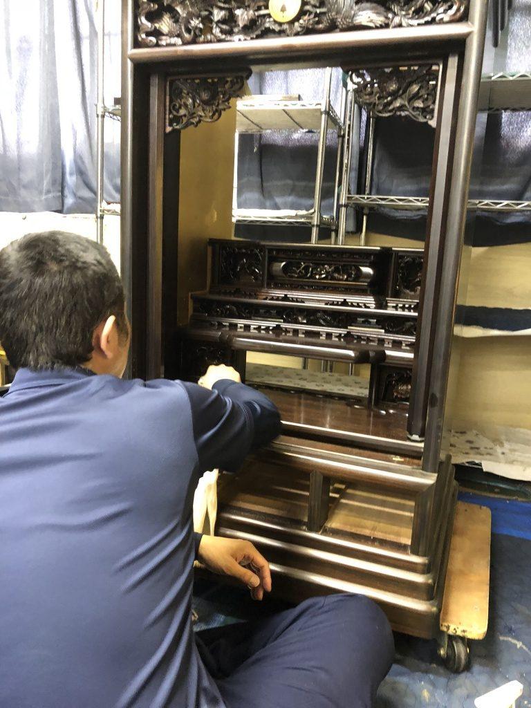 唐木専用の木部表面の汚れを洗い流す特殊なアルコール溶剤を使って、木部表面に付着した油煙やホコリなどを最終的に完全に取り除いていきます。左画像がその様子ですが、泡の下の方が茶色唐木専用の木部表面の汚れを洗い流す特殊なアルコール溶剤を使って、木部表面に付着した油煙やホコリなどを最終的に完全に取り除いていきます。左画像がその様子ですが、泡の下の方が茶色くなっています。これが、お仏壇に付着した油煙(よごれ)であり、まずは、汚れの除去をしっかりと行います。